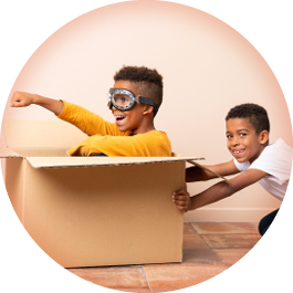 Boys playing in box using imagination.