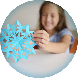 Girl holding up blue snowflake.