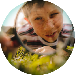 Boy using magnifying glass outside to examine grass.