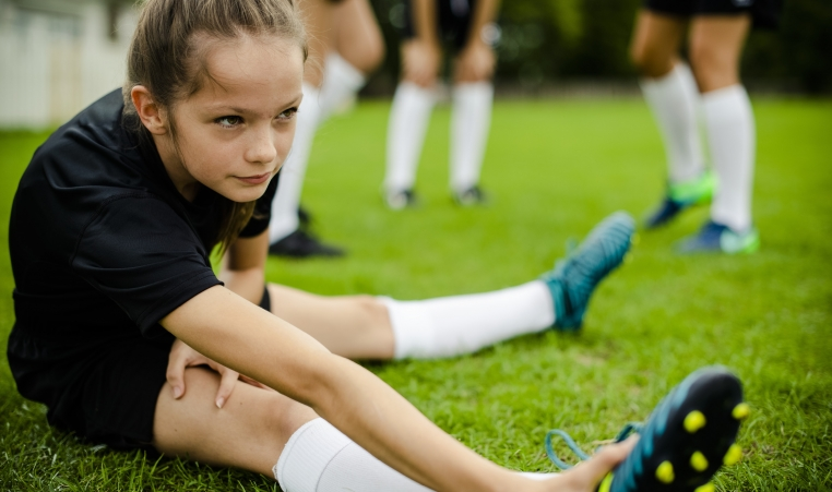 Girl stretching before soccer as part of a YMCA youth sports progam for girls