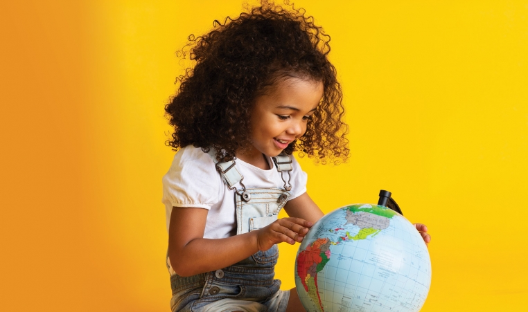 Young girl at a world globe