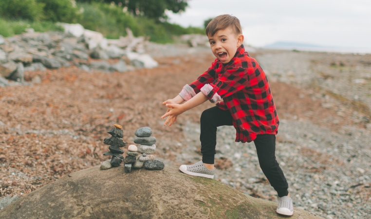 Boy showing off his rock stacks at the beach.