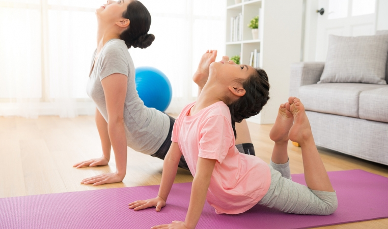 A mom and daughter practicing yoga at home