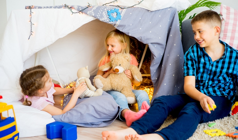 Three kids playing in living room tent
