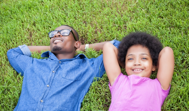 Dad and daughter laying on grass with hands behind head