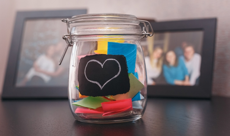 Colorful notes in a glass jar with a heart