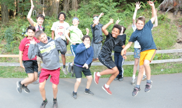 A group of boy campers being silly and jumping for a photo