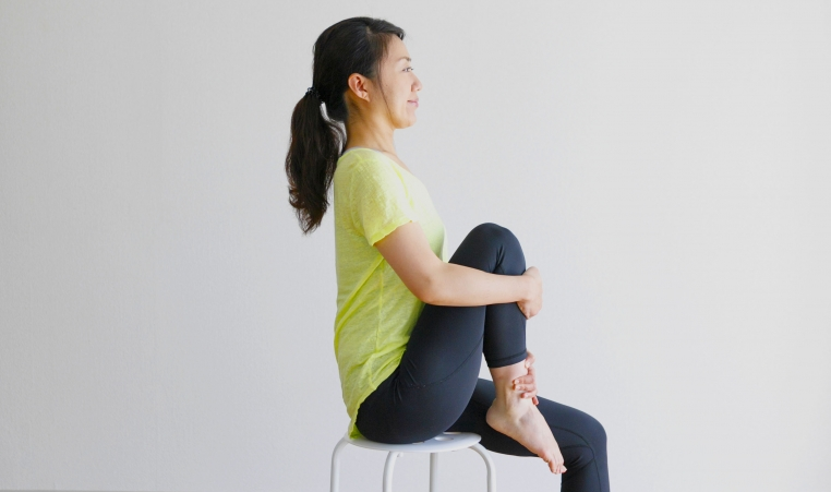 Women sitting on chair with knee in air and foot lifted doing a stretch