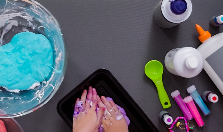Child's hands squishing homemade purple slime, surrounded by all the tools used.