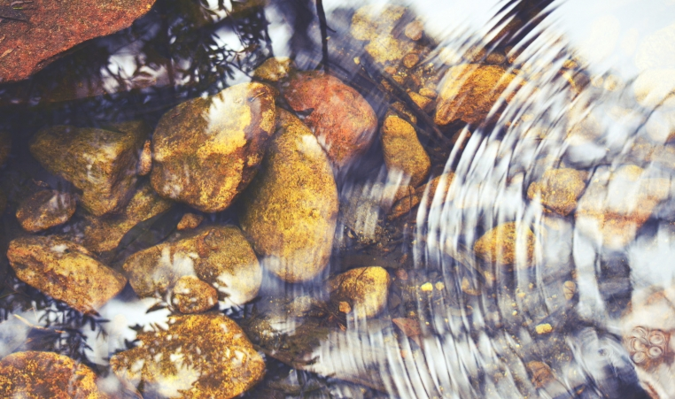 Rocks in stream creating small water vibration ribbons