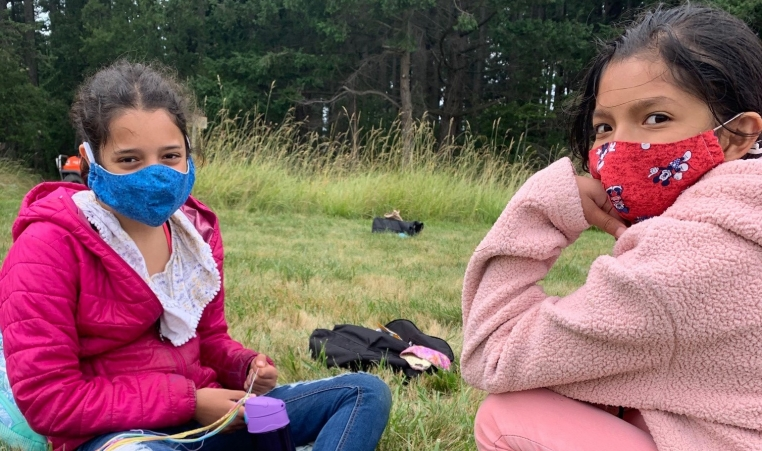 Two girls sitting across from eachother outside in a field with face masks on.