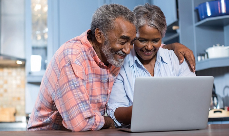 Man and woman looking at laptop screen together.
