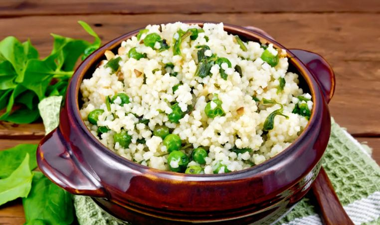 Cous Cous with green peas in a brown bowl