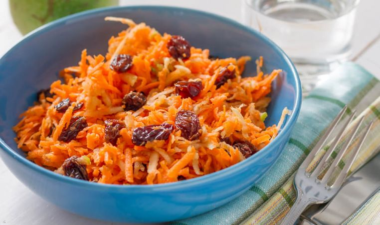 Orange shaved carrots with raisins in a blue bowl