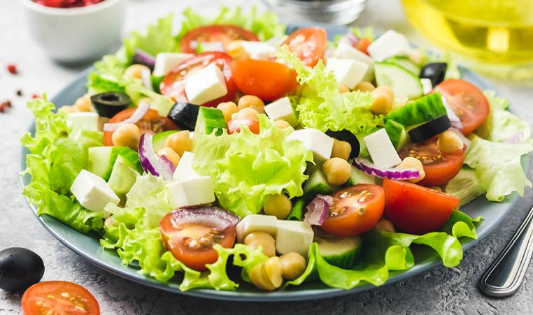 Salad with tomatoes, cucumbers, cheese, red onion, chickpeas, olives