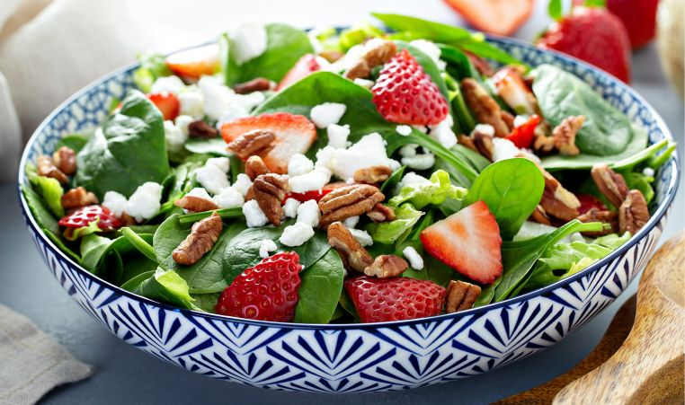 Spinach Strawberry Salad in blue and white bowl with goat cheese and candied pecans