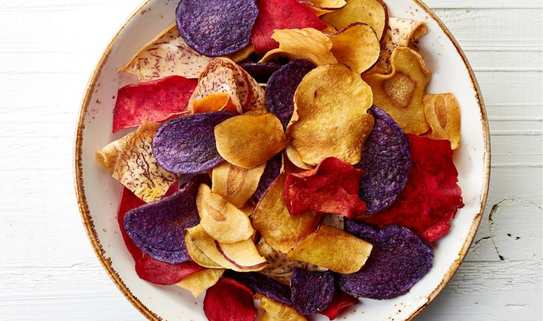 Purple, red and yellow roasted veggie chips served on a white plate with a gold rim