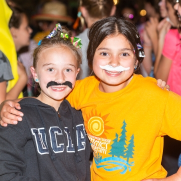 Girls with silly mustaches at camp