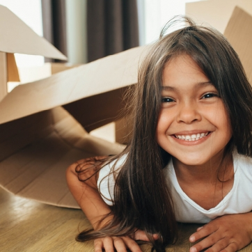 Girl smiling as she crawls out of a box