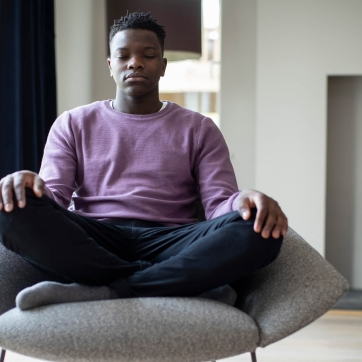 Man sitting on chair with closed eyes meditating