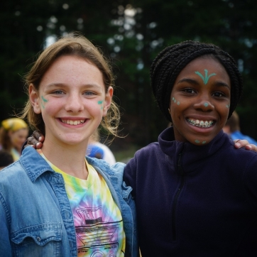 Two teen girls with painted faces at camp.