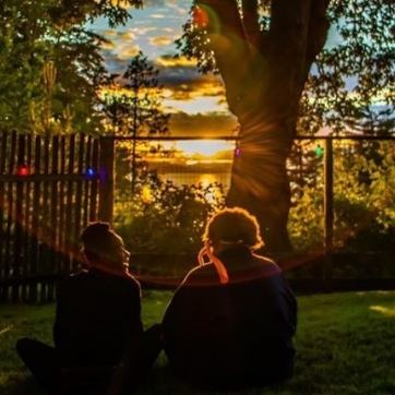 Two friends sitting in the evening sun, watching the sunset over the water and trees