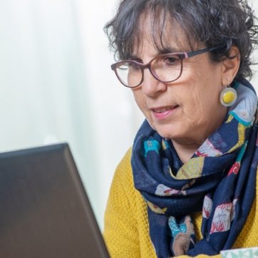 Active Older Adult woman with blue patterned scarf and yellow sweater doing work on her laptop