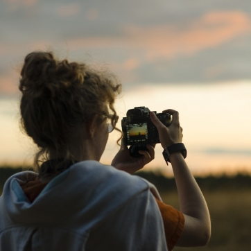 Woman taking photo of sunset, with camera screen showing her view