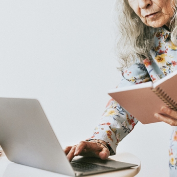 Woman in flower shirt looking at pink notebook while typing on laptop