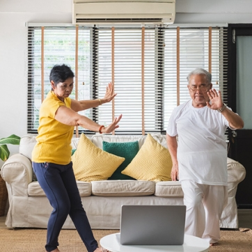 Grandparents dancing to a virtual class on their laptop.