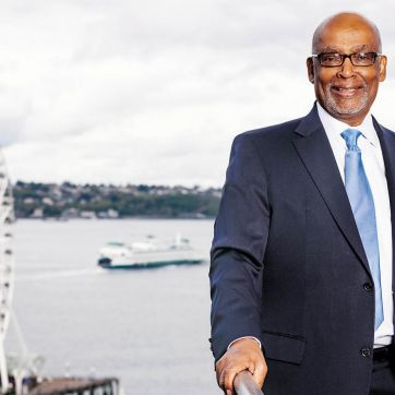 Photo of Norm Rice with Seattle waterfront in the background.
