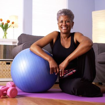 Black-presenting woman sitting on a yoga mat in her home