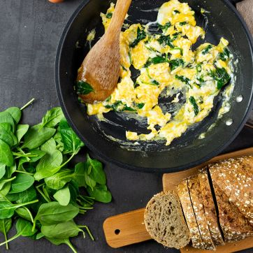 Scrambled eggs with spinach in a black skillet with a wooden spoon. Whole leaves of spinach and a loaf of wheat bread on a wooden serving plate in the background.