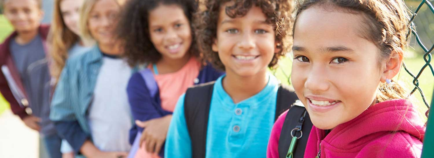 A group of children smiling with backpacks on