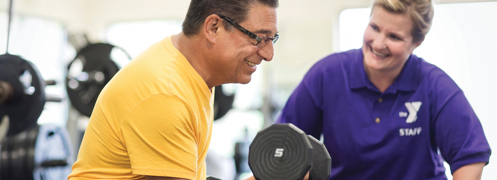 An adult curling a dumbbell at a LIVESTRONG® at the YMCA program