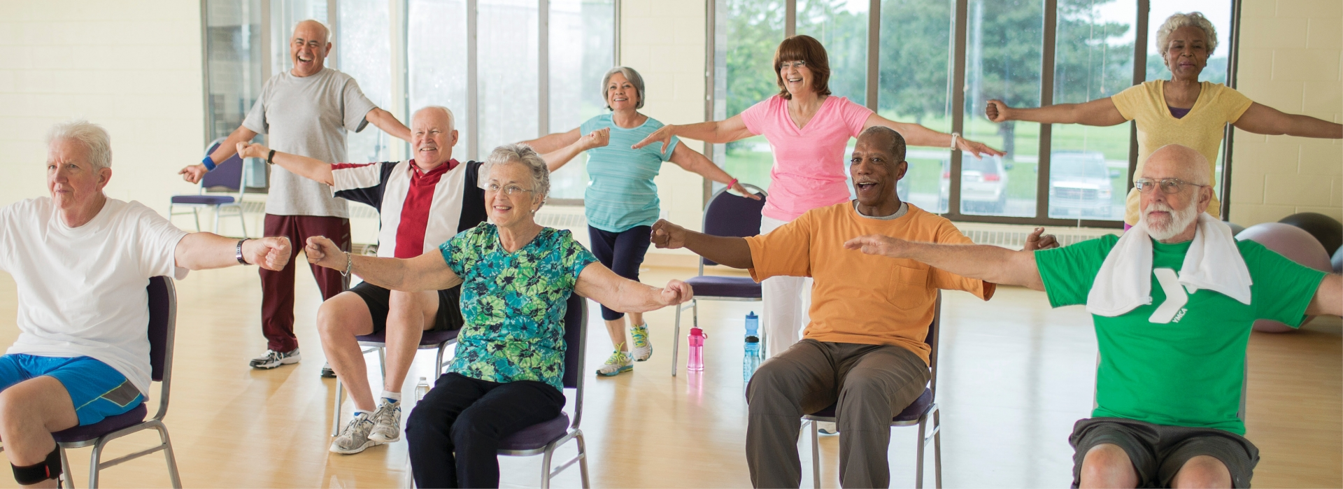 A group of adults exercise in a YMCA program for health