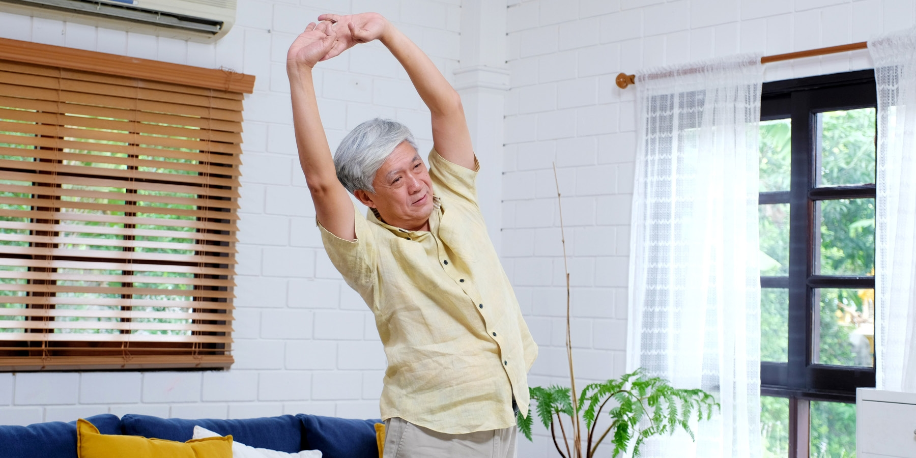 Older gentleman stretching with arms above head