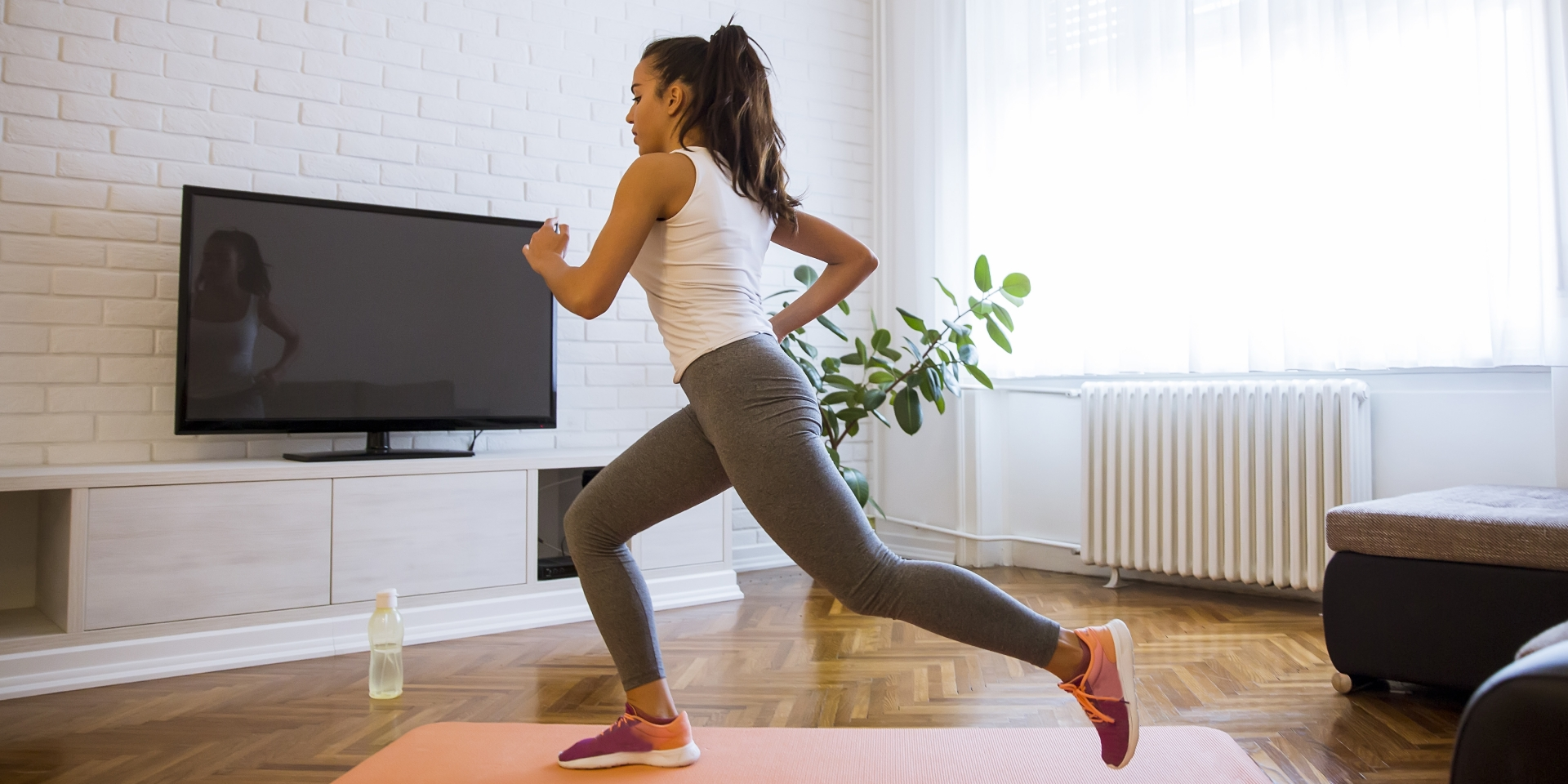 Woman working out in home on yoga mat in front of tv
