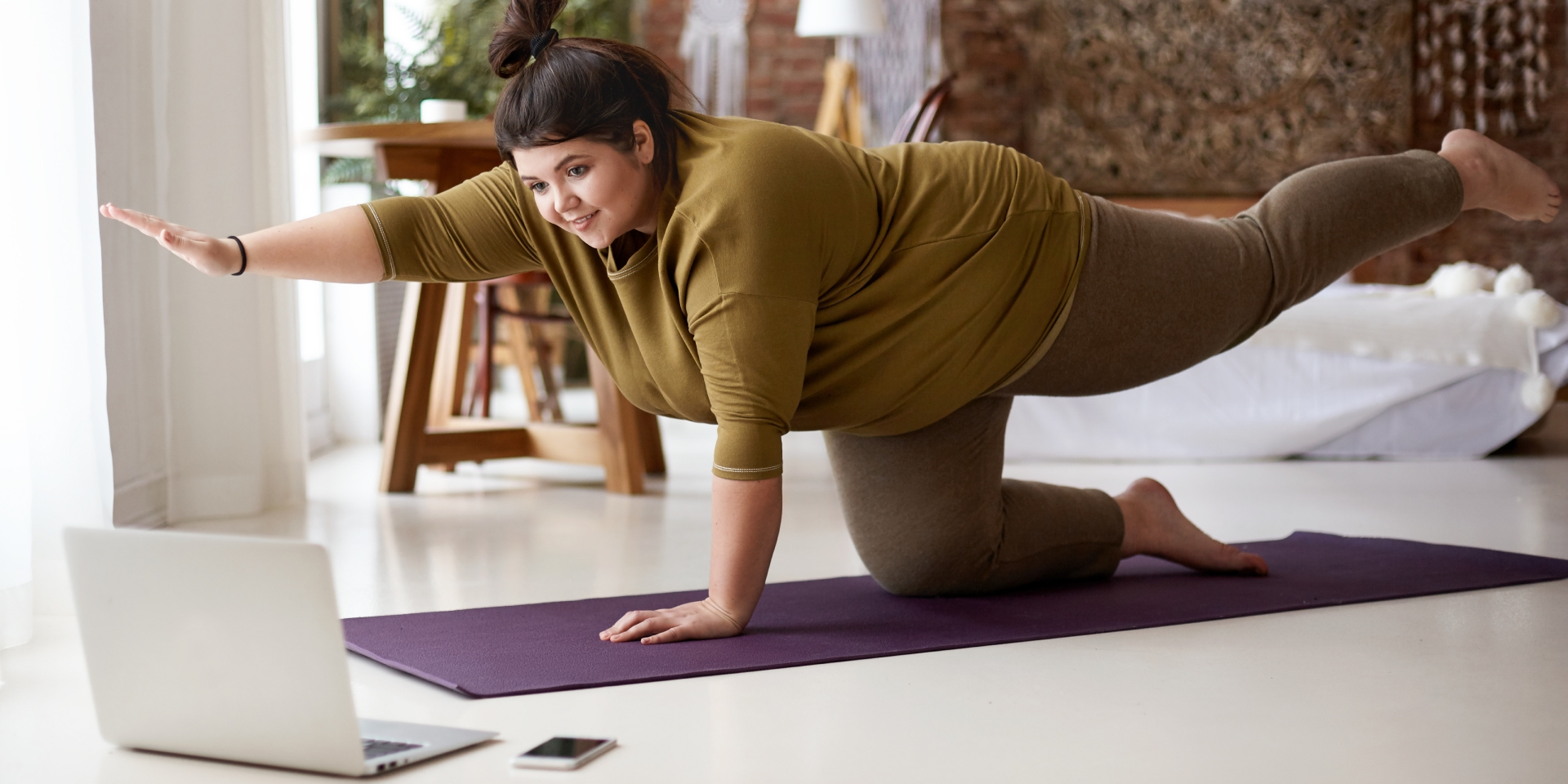 Woman on mat, doing a yoga move as demonstrated on her computer