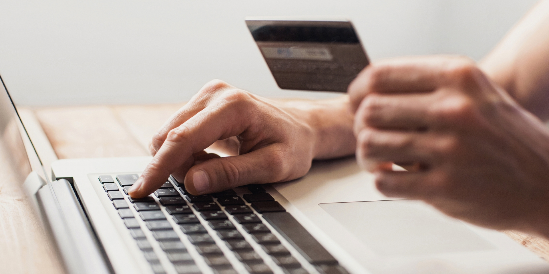 Close up of man typing on laptop with credit card in other hand.