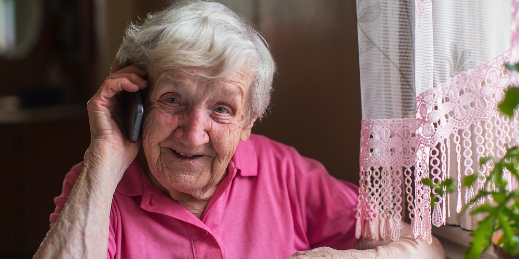 Older woman in pink shirt talking on the phone