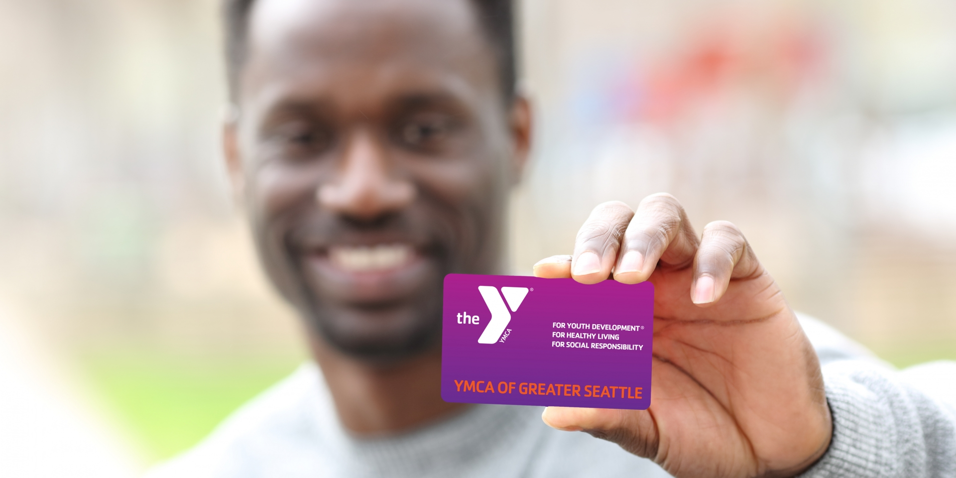 Man holding up his Y membership card.