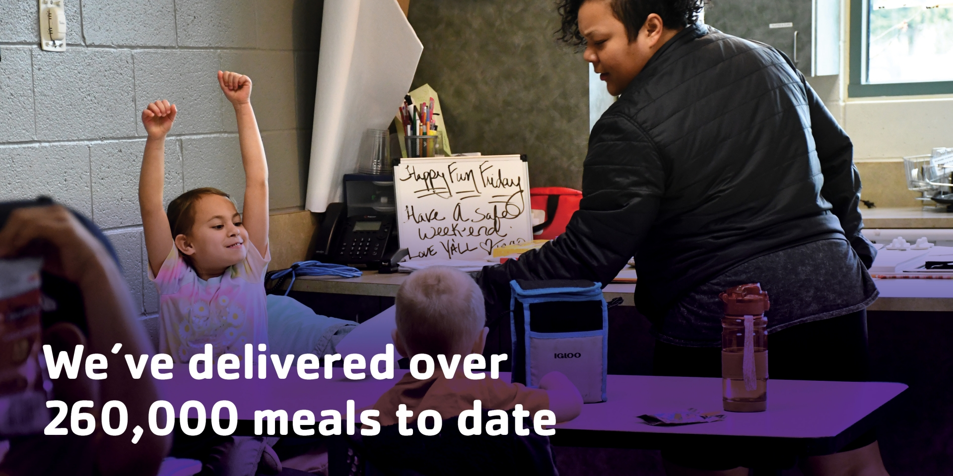 Child receiving meal from Y staff. Text reads, We've delivered over 260,00 meals to date