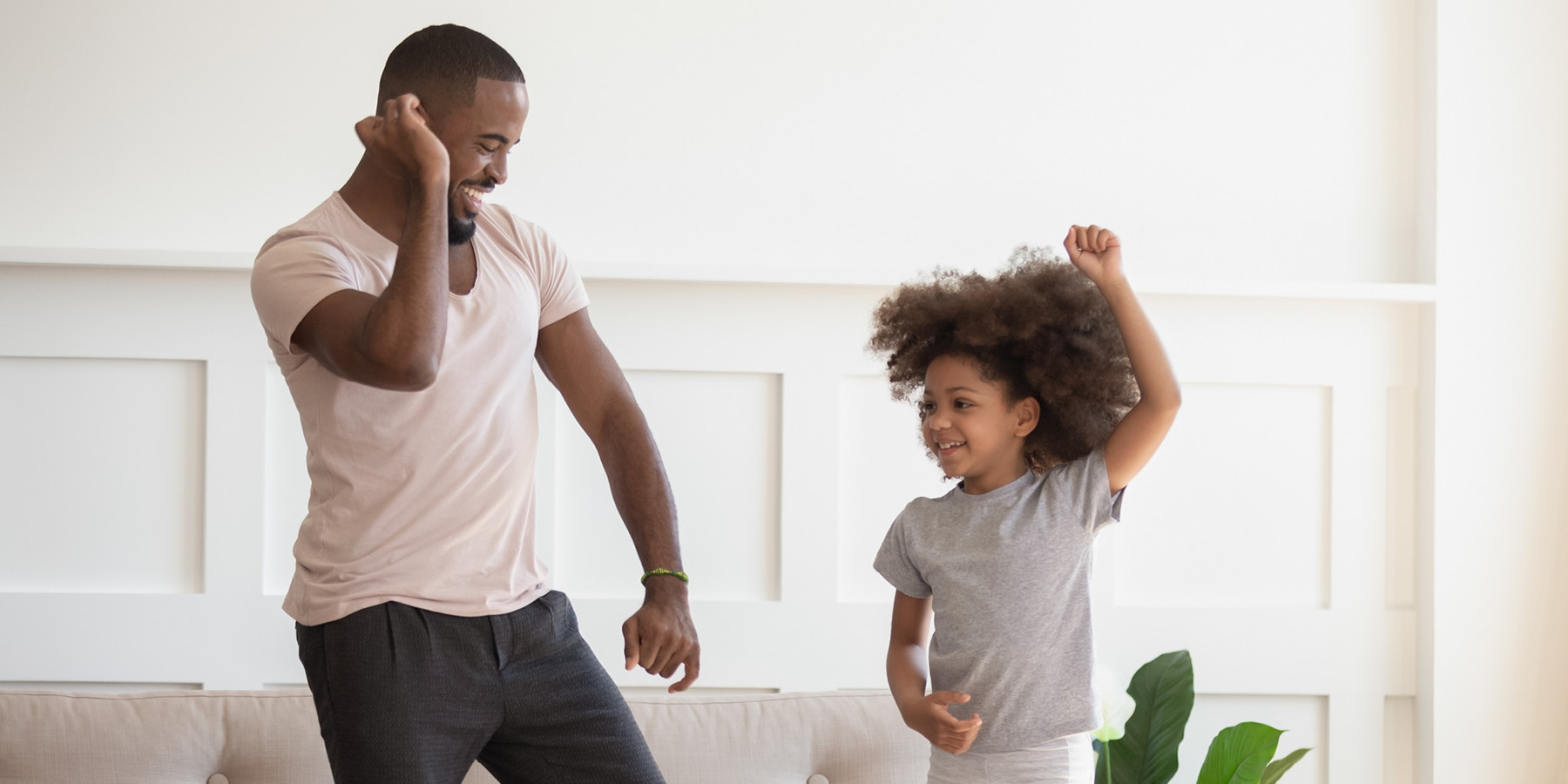 Father and daughter dancing in living room