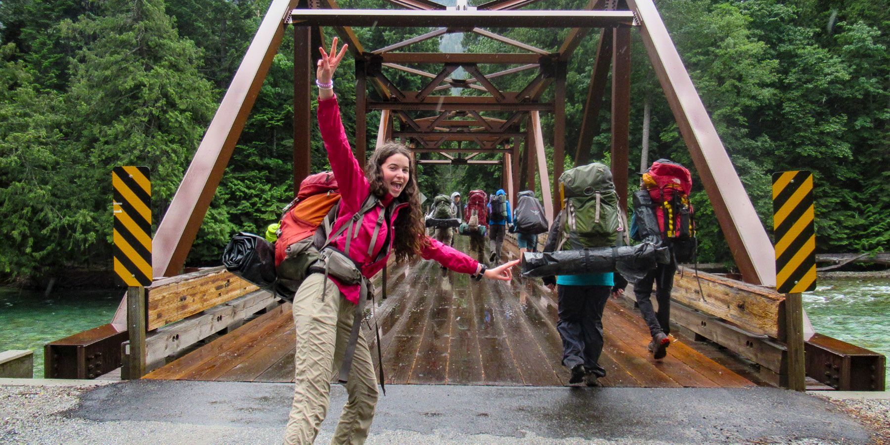 Teen girl happy as she crosses a bridge into the wilderness with friends.