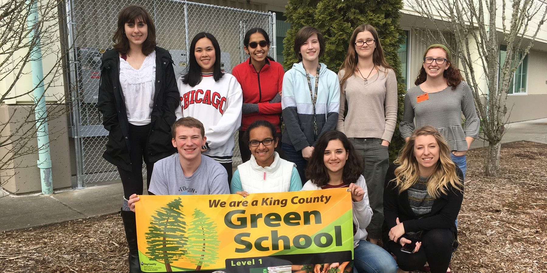 "Teens posing outside school with banner that says, ""We are a green school"""