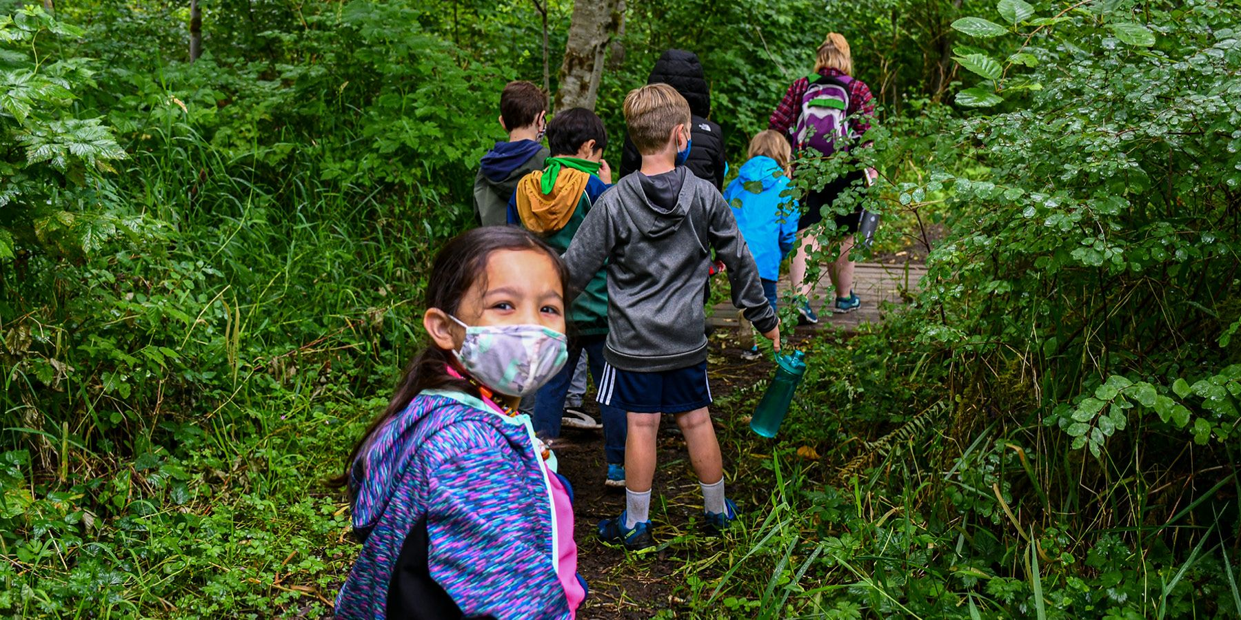Group of day campers on a trail, wearing masks