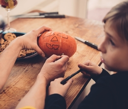 Adult teaching child how to carve a pumpkin