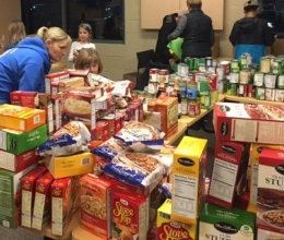 Mother and Daughter standing near table full of non-perishable food for Food Bank.