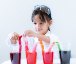 Girl with safety goggles on her head doing a science experiment with cups of colored water